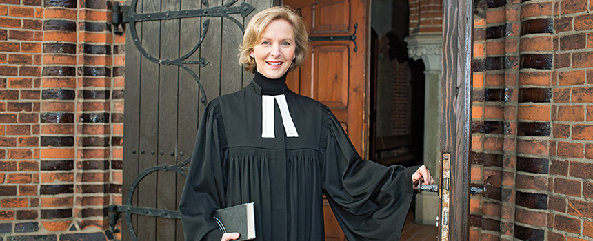 Pastorin vor Kirche